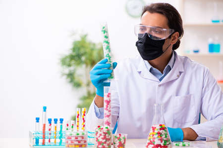Young male chemist in drug synthesis concept Banque d'images - 143287105