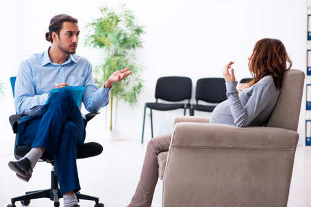 Pregnant woman visiting young male psychologist