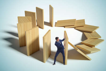Businessman in the domino effect concept