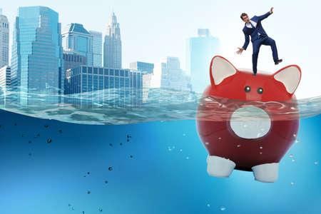 The businessman in debt concept with piggybank