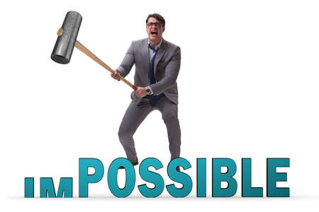 Businessman hitting the word impossible with hammer