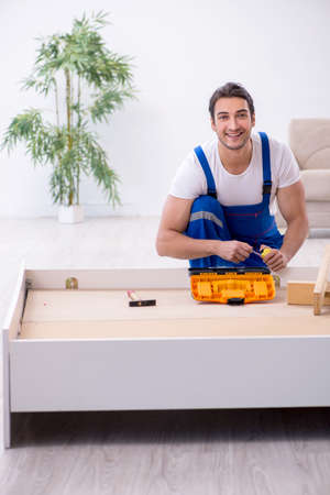 Young male contractor installing furniture at home 版權商用圖片