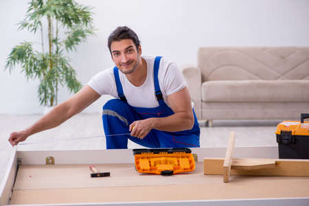 Young male contractor installing furniture at home 版權商用圖片 - 143744046