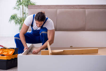 Young male contractor installing furniture at home 版權商用圖片 - 143744047