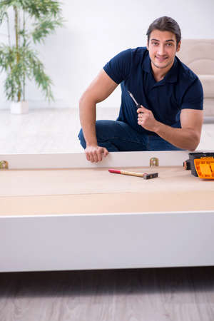 Young male contractor installing furniture at home 版權商用圖片 - 143711403