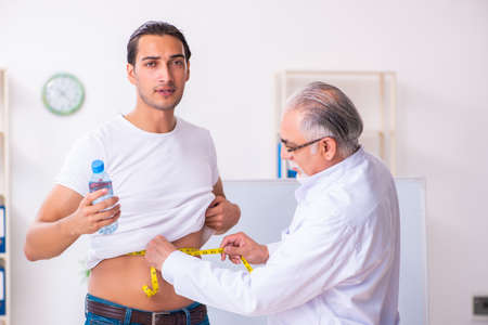 Doctor dietician giving advices to fat overweight patient Stock Photo