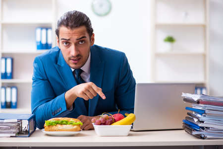 Young male employee having breakfast at workplace