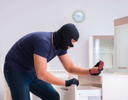 Robber wearing balaclava stealing valuable things 스톡 콘텐츠