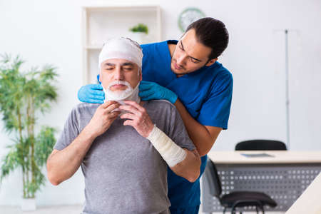 Young male doctor and old patient in first aid concept