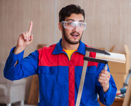 Young repairman carpenter working with clamps 版權商用圖片