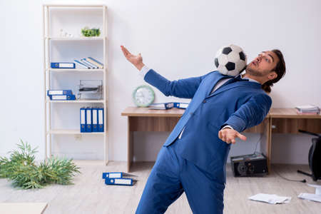 Young male employee playing football in the office
