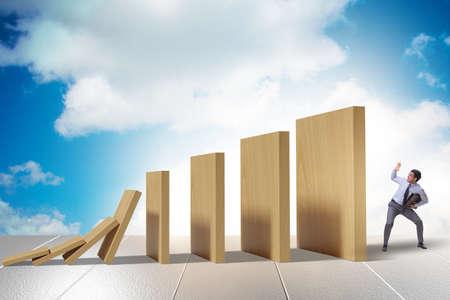Businessman in domino effect concept Stockfoto