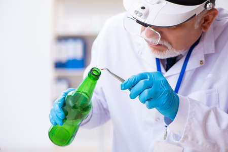 Old expert criminologist working in the lab for evidence Stock Photo