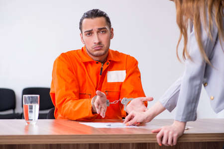 Young man meeting with advocate in pre-trial detention Banque d'images