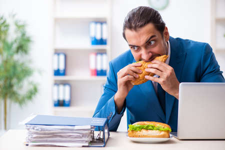 Young male employee having breakfast at workplace Stock Photo