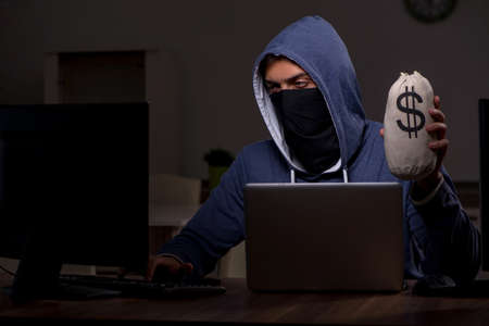 Male hacker hacking security firewall late in office