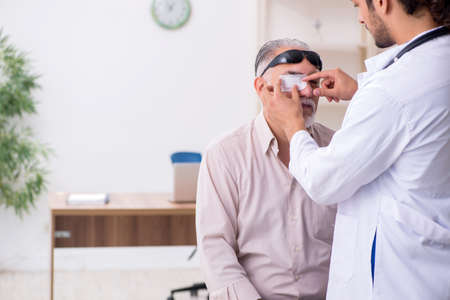 Old man visiting young male doctor Imagens