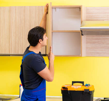 Young service contractor assembling kitchen furniture 写真素材