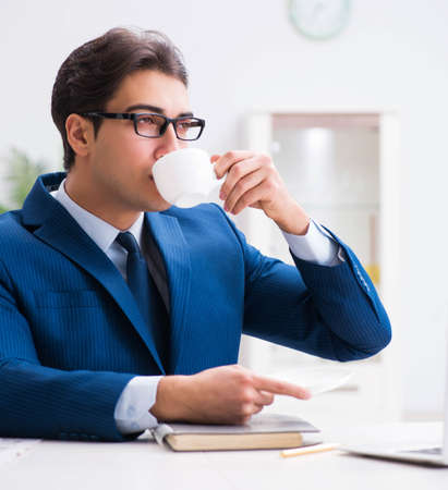 Young handsome businessman drinking coffee in the office