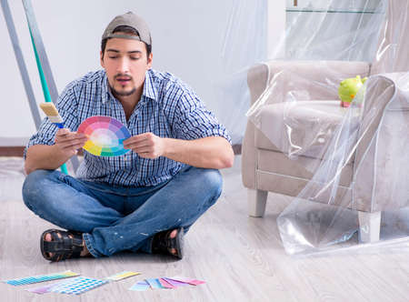 Young man contractor choosing color from rainbow Stockfoto