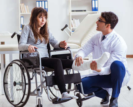 Médico varón examinando a paciente en silla de ruedas