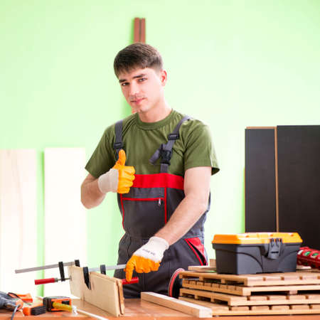 Young man carpenter working in workshop Banque d'images