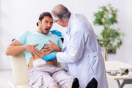 Injured young man visiting experienced male doctor Archivio Fotografico