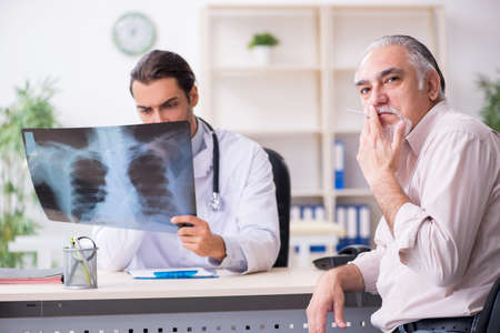 Young male doctor and old patient in antismoking concept Imagens