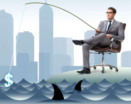 Businessman fishing out dollars from water Stock Photo