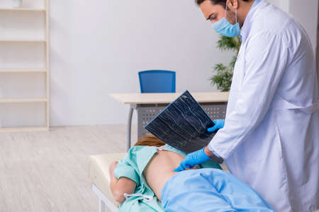 Young injured woman visiting male doctor chiropractor