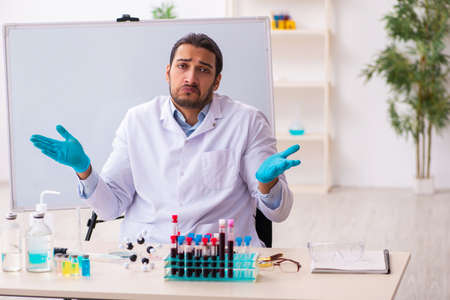 Young male chemist working in the lab Imagens