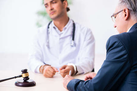 Male doctor in courthouse meeting with lawyer