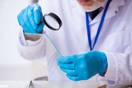 Old expert criminologist working in the lab for evidence Archivio Fotografico