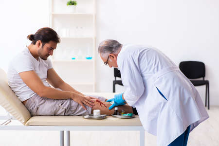 Leg injured man visiting old doctor in first aid concept Foto de archivo