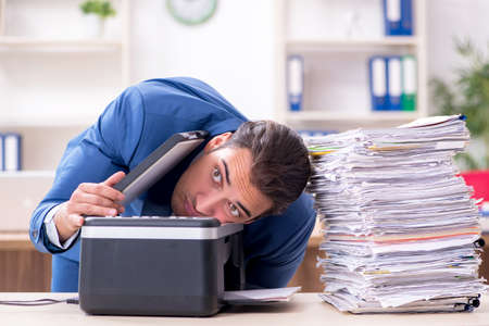 Young male employee making copies at copying machine