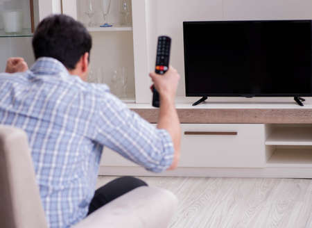 The young man watching tv at home