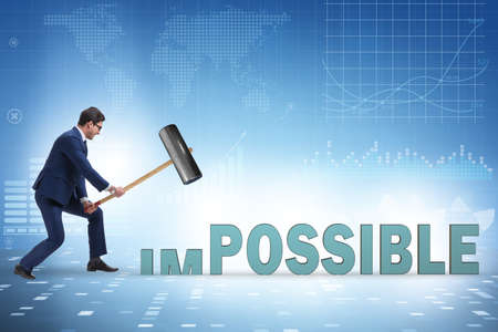 Businessman hitting the word impossible with hammer Banque d'images
