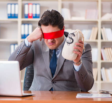 The blindfold businessman sitting at desk in office