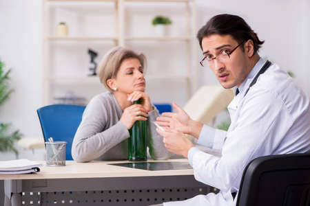 Female alcoholic visiting young male doctor