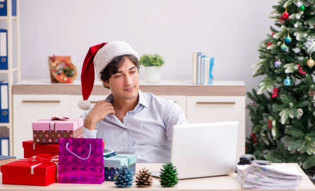 Young employee businessman in office christmas concept