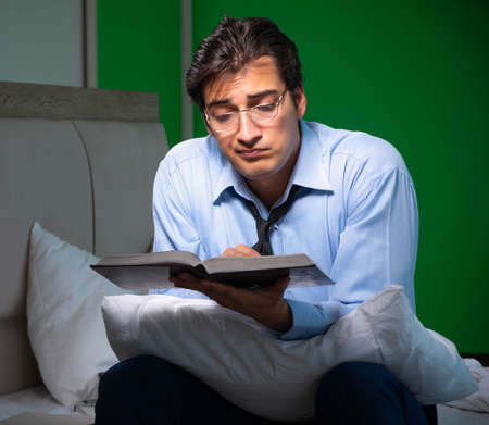 Young businessman under stress in the bedroom at night