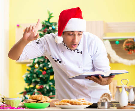 Young chef husband working in kitchen at Christmas eve