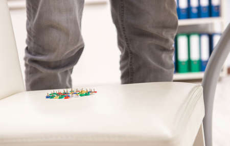 The office prank with sharp thumbtacks on chair Stock Photo