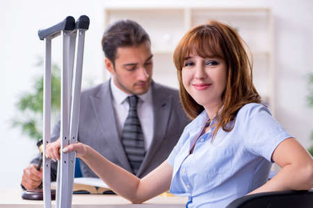 Young injured woman and male lawyer in the courtroom