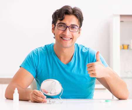 Man trying contact lenses at home