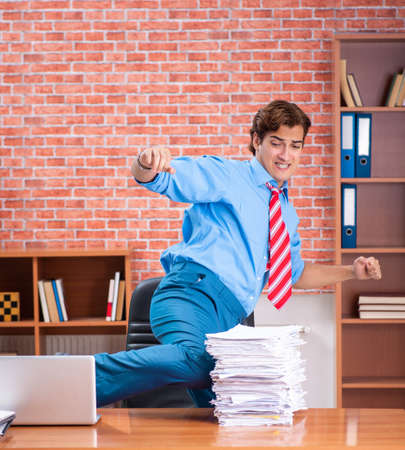 Young employee with excessive work sitting at the office Stock Photo