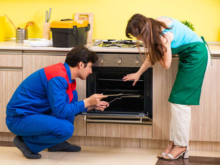 Woman with contractor at kitchen discussing repair