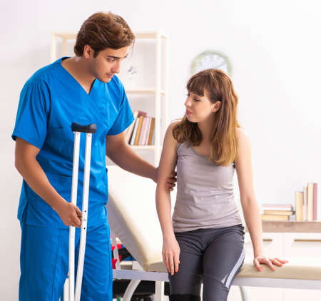 Young female patient visiting male doctor traumatologist Stock Photo
