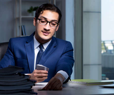 Young business playing cards late in office Foto de archivo