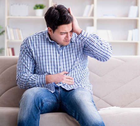 Sick man suffering at home from infection and bad stomach Stockfoto